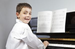 Boy playing the piano with sheet music.